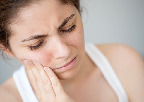 Woman with TMJ disorder considers orthodontic braces from Sawrie Orthodontics to treat jaw pain
